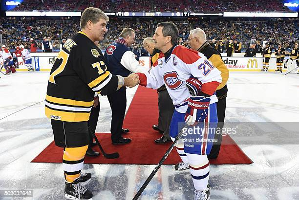 Ray Bourque of the Boston Bruins Alumni Team and Guy Carbonneau of the Montreal Canadiens shake hands prior to the Alumni Game as part of the 2016...