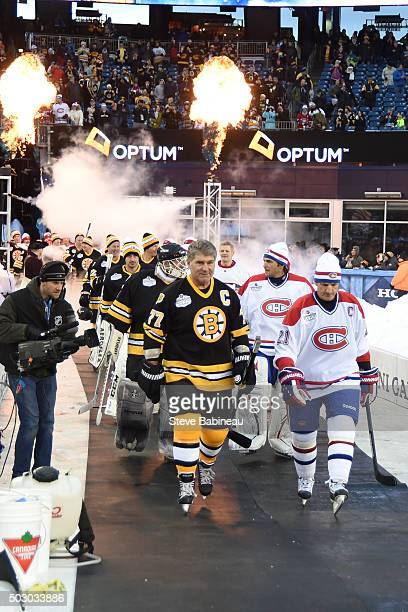 Ray Bourque of the Boston Bruins and Guy Carbonneau of Montreal Canadiens walk out to the ice for the alumni game on December 31 2015 during 2016...