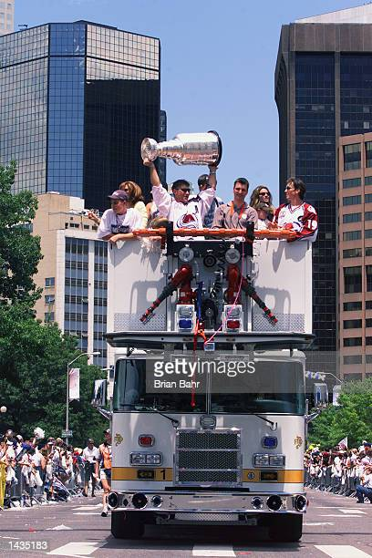 Ray Bourque of the Colorado Avalanche hoists the Stanley Cup over his head as Joe Sakic watches to celebrate winning the 2001 NHL Stanley Cup...