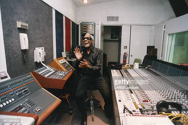 Ray Charles At Home In Los Angeles Closeup Attitude riante de Ray CHARLES assis dans son studio d''enregistrement devant une grande table de mixage...