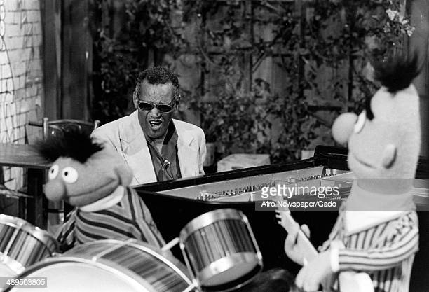 Ray Charles blind musician and blues singer seated playing the keyboard on the set of the children's television programme Sesame Street with a puppet...