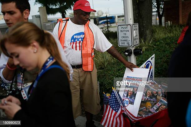 Ray Collins of Southern Pines sells programs and flags as delegates guests and young Republicans make their way into the Tampa Bay Times Forum on the...