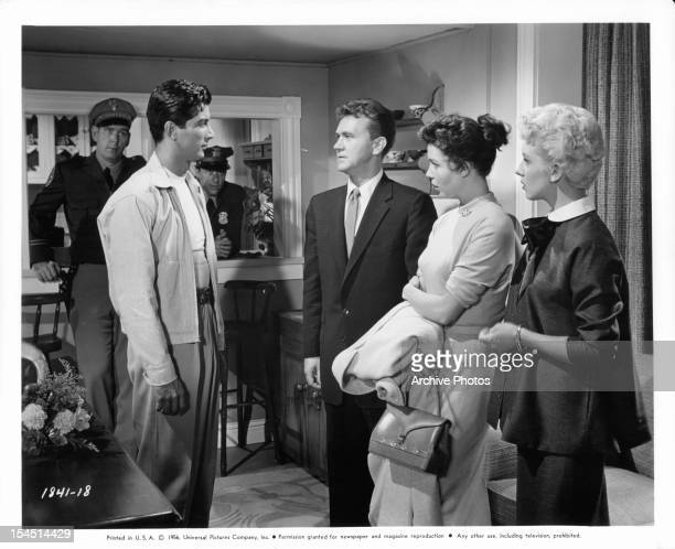 Ray Danton is questioned by Harry Jackson as Colleen Miller and Merry Anders watch in a scene from the film 'The Night Runner' 1957