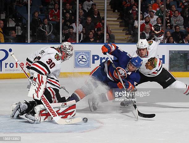 Ray Emery and defenseman Niklas Hjalmarsson of the Chicago Blackhawks defend against John Tavares of the New York Islanders at the Nassau Veterans...