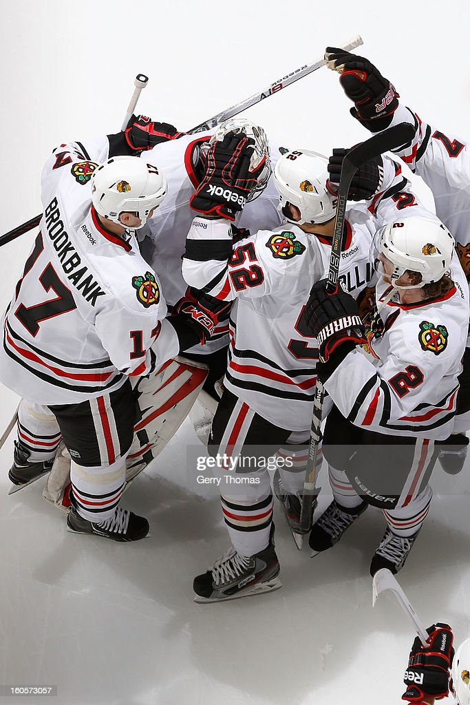 Ray Emery #30 is congratulated by teammates of the Chicago Blackhawks for a 3-2 shootout win against the Calgary Flames on February 2, 2013 at the Scotiabank Saddledome in Calgary, Alberta, Canada.