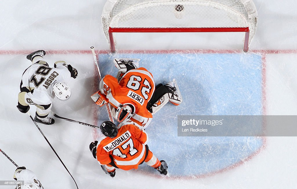 Ray Emery #29 of the Philadelphia Flyers covers the puck as teammate Andrew MacDonald #47 defends against Sidney Crosby #87 of the Pittsburgh Penguins on January 20, 2015 at the Wells Fargo Center in Philadelphia, Pennsylvania. The Flyers went on to defeat the Penguins 3-2 in overtime.