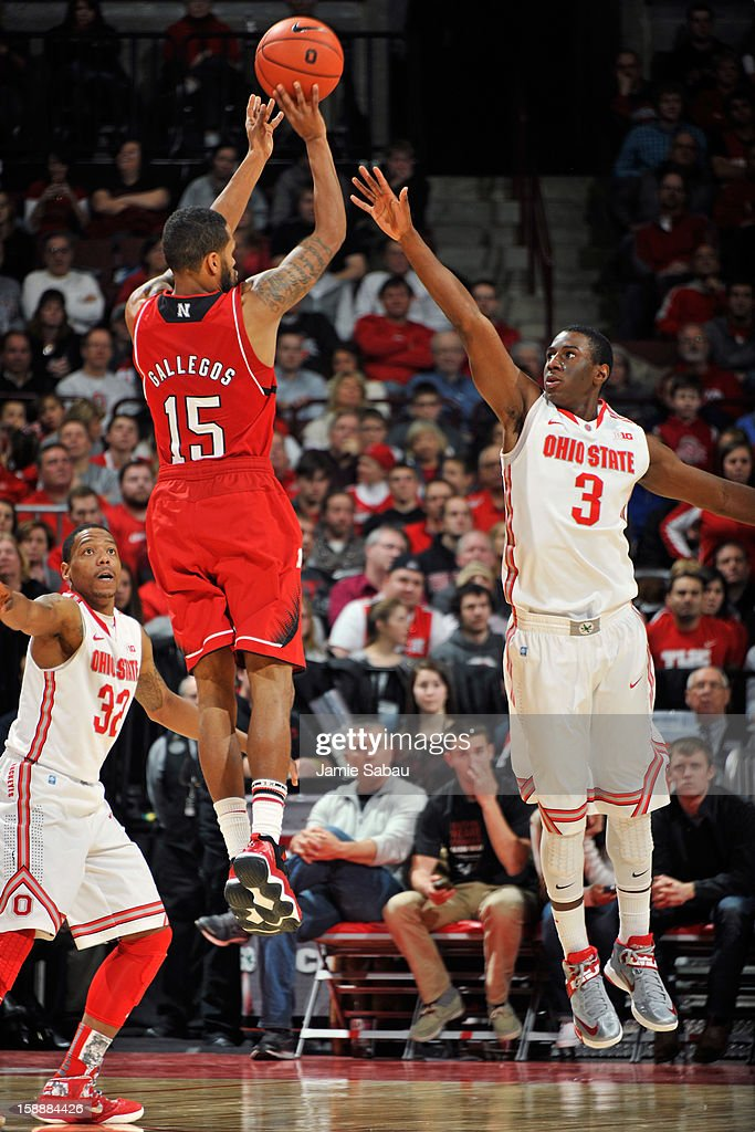 Ray Gallegos #15 of the Nebraska Cornhuskers attempts a three-point shot over the defense of Shannon Scott #3 of the Ohio State Buckeyes in the second half on January 2, 2013 at Value City Arena in Columbus, Ohio. Ohio State defeated Nebraska 70-44.