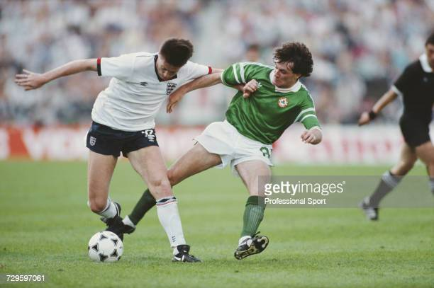 Ray Houghton of the Republic of Ireland moves in to tackle Chris Waddle of England for the ball during play in the group 2 match between England and...