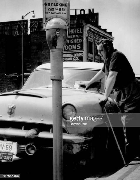Ray Krolicki disabled World War II veteran and Denver Post staff artist eyes the parking ticket hung on his car early Monday as police began their...