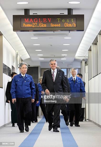 Ray LaHood, U.S. Transportation secretary, center, accompanied by Yoshiyuki Kasai, chairman of Central Japan Railway Co., left, walks on the platform...