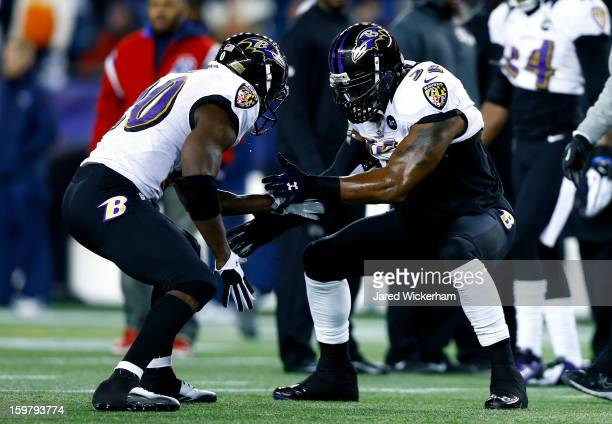 Ray Lewis of the Baltimore Ravens highfives teammate Ed Reed on the field prior to the 2013 AFC Championship game against the New England Patriots at...