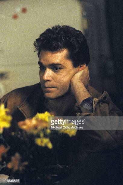 Ray Liotta leaning on palm in front of flowers in a scene from the film 'Dominick And Eugene' 1988