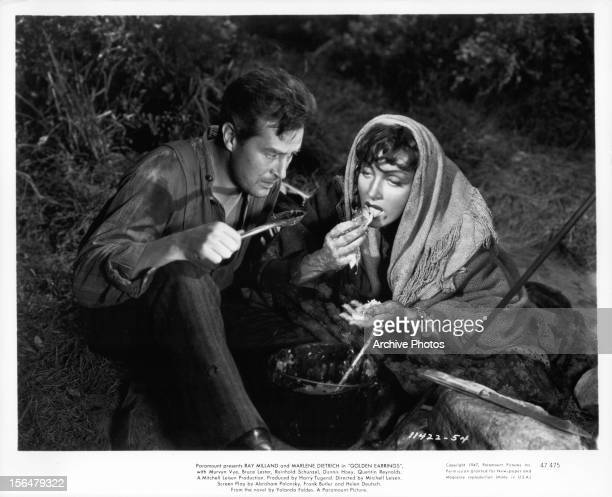 Ray Milland and Marlene Dietrich eating from pot outside in a scene from the film 'Golden Earrings', 1947.