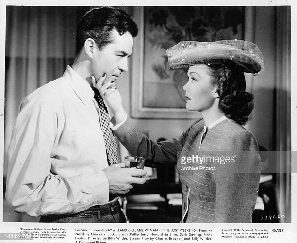 Ray Milland holding drink as Jane Wyman holds his chin in a scene from the film 'The Lost Weekend' 1945