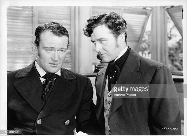 Ray Milland looking at John Wayne in a serious manner in a scene from the film 'Reap The Wild Wind', 1942.