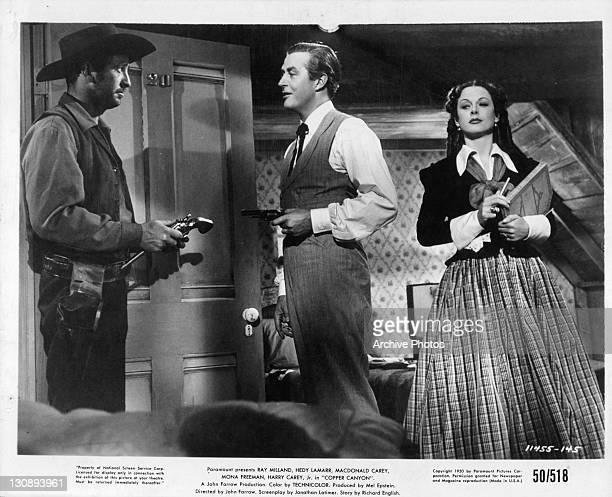 Ray Milland pointing his gun at unidentified man while Hedy Lamarr is close by in a scene from the film 'Copper Canyon' 1950