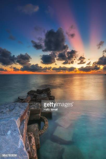 ray of light sunset at mabul island - mabul island stock photos and pictures