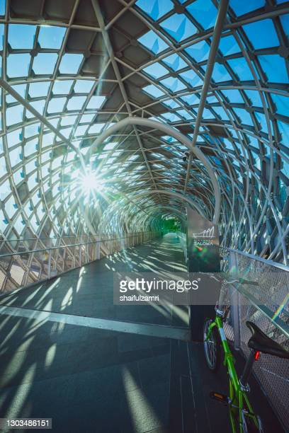 ray of morning light from saloma link; a 69 metres combined pedestrian and bicyclist bridge across the klang river in kuala lumpur. directed northwest to southeast it joins the districts of kampung baru and kuala lumpur city centre. - shaifulzamri fotografías e imágenes de stock
