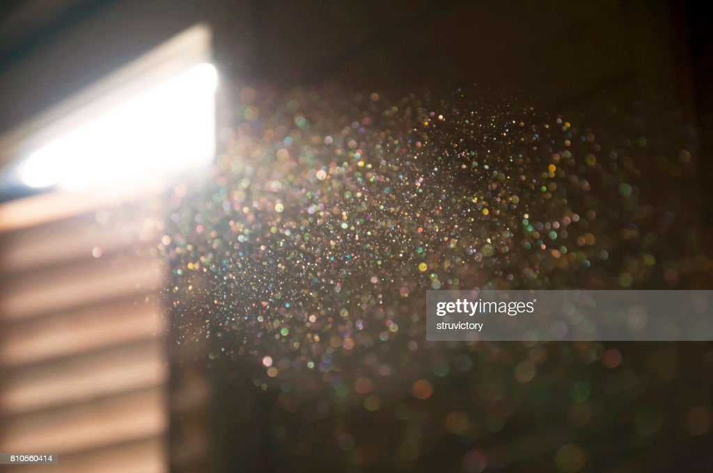 A ray of sun coming through the wooden shutters, illuminates dust on the inside of a dark room. : Stock Photo