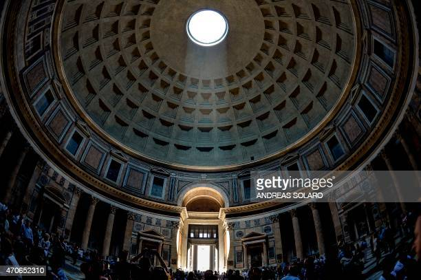 A ray of sunlight illuminates the central door of the Pantheon through the dome on April 21 2015 AFP PHOTO / ANDREAS SOLARO
