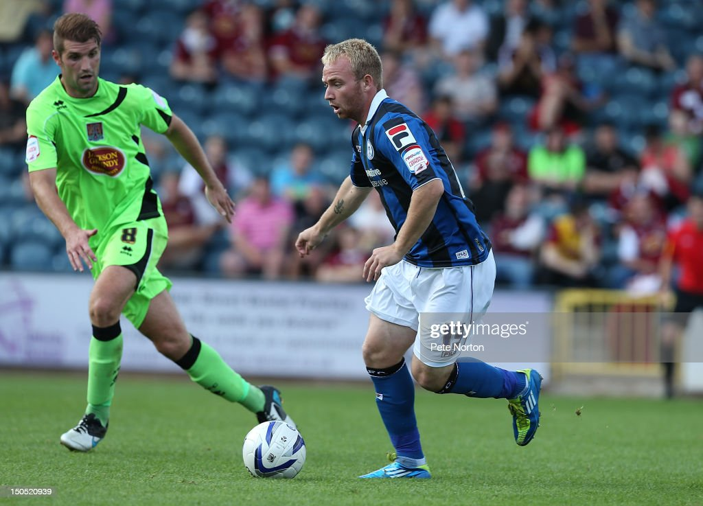 Ray Putterill of Rochdale moves forward with the ball watched by Ben Harding of Northampton Town during the npower League Two match between Rochdale and Northampton Town at Spotland Stadium on August 18, 2012 in Rochdale, England.