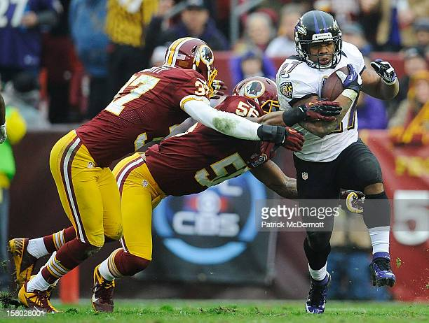 Ray Rice of the Baltimore Ravens breaks the tackles of Perry Riley and Reed Doughty of the Washington Redskins in the second quarter of a game at...