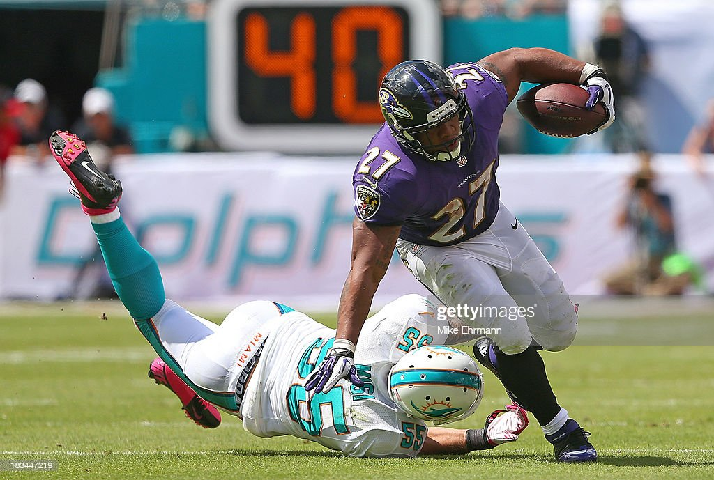 Ray Rice #27 of the Baltimore Ravens is tackled by Koa Misi #55 of the Miami Dolphins during a game at Sun Life Stadium on October 6, 2013 in Miami Gardens, Florida.