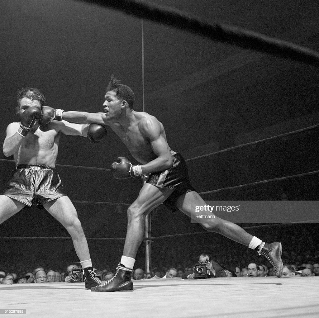 Ray Robinson, Harlem's 'uncrowned welter champ,' connects with a long right to Jake LaMotta's head at Madison Square Garden.