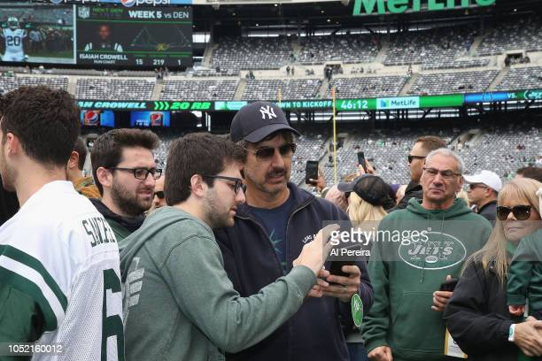 Ray Romano gets instruction on how to take a selfie from his sons Matthew Romano and Gregory Romano at the Indianapolis Colts vs New York Jets game...