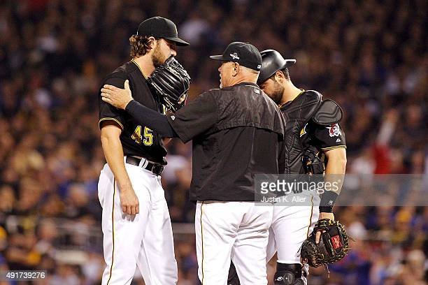 Ray Searage of the Pittsburgh Pirates talks with Gerrit Cole of the Pittsburgh Pirates and Francisco Cervelli of the Pittsburgh Pirates on the...