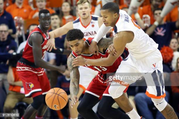 Ray Spalding of the Louisville Cardinals knocks the ball away from Devon Hall of the Virginia Cavaliers in the first half during a game at John Paul...