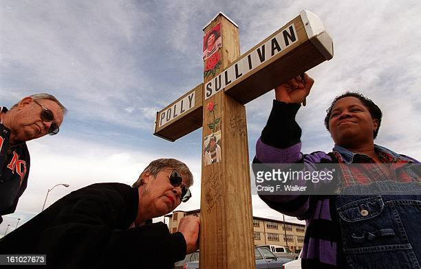 Ray Studer watches as his wife Millie and Crooked Tree resident Spesal Flanagan sign a cross outside the apartment complex honoring Polly Sullivan...