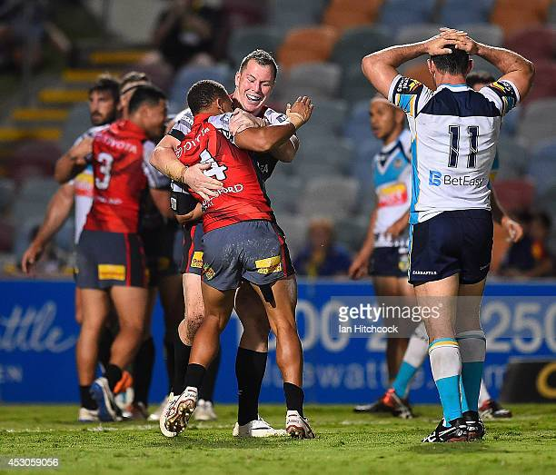 Ray Thompson and Glenn Hall of the Cowboys celebrate the try of Tautau Moga during the round 21 NRL match between the North Queensland Cowboys and...