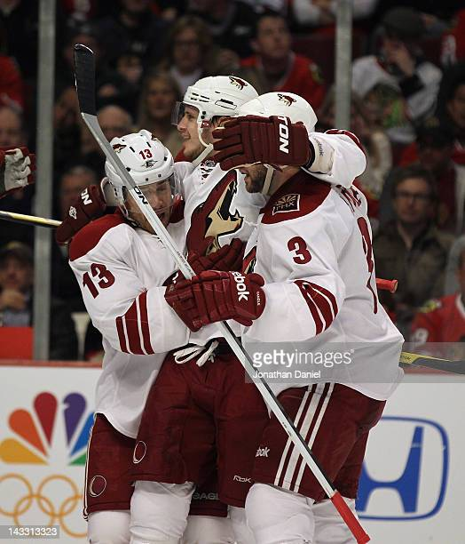Ray Whitney and Keith Yandle of the Phoenix Coyotes hug teammate Oliver Ekman-Larsson after Larsson scored a second period goal against the Chicago...