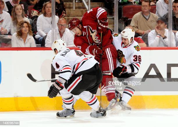 Ray Whitney of the Phoenix Coyotes and Niklas Hjalmarsson and Dave Bolland of the Chicago Blackhawks fight for control of the puck in Game Five of...