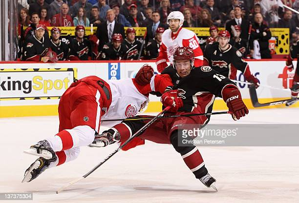 Ray Whitney of the Phoenix Coyotes is checked by Brad Stuart of the Detroit Red Wings during the second period of the NHL game at Jobingcom Arena on...