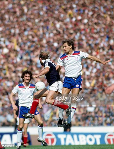 Ray Wilkins of England jumps higher than Archie Gemmill of Scotland watched by England's Terry McDermott during the Home International Championship...