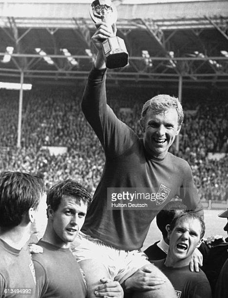 Ray Wilson and Geoff Hurst carry Bobby Moore as he celebrates England's victory in the 1966 Soccer World Cup at Wembley London
