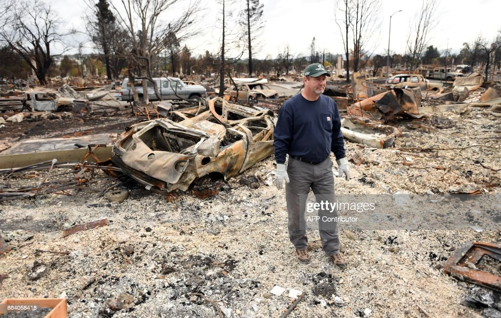 Ray Wilson views his burned home in the Coffey Park area of Santa Rosa, California, on October 20, 2017. Residents are being allowed to return to their burned homes on October 20 to grieve and search through remains. Around 5,700 homes and businesses have been destroyed by the fires, the deadliest in California's history. /