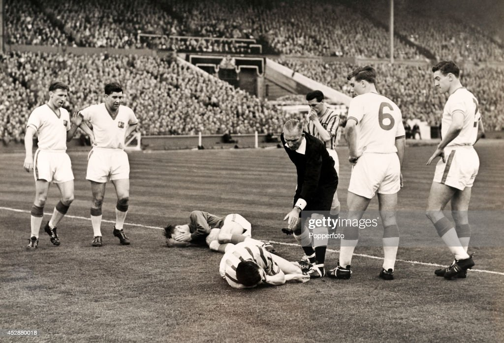 Ray Wood, Manchester United goalkeeper (on the floor, left), with a fractured jaw brought about by his collision with Peter McParland of Aston Villa (on the ground, right) during the FA Cup Final at Wembley Stadium in London on 4th May 1957. The Manchester United players (white shirts) are, left to right: Roger Byrne, Jackie Blanchflower, Duncan Edwards (6) and Bill Foulkes. Aston Villa won 2-1.