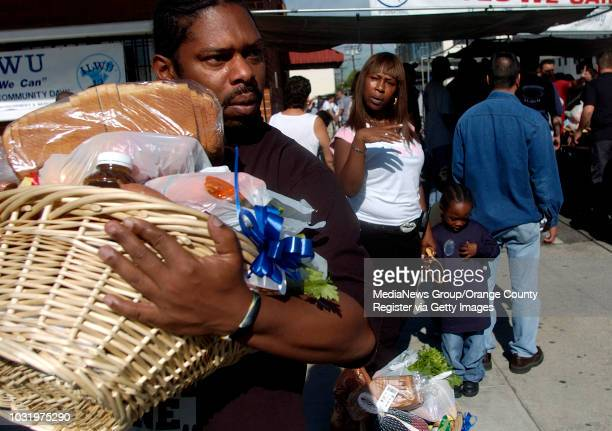 11/22/05 Ray Young left of Long Beach and his girlfriend Caprice Carter and her son John gather their food during the ILWU's 8th Annual 'Feed the...