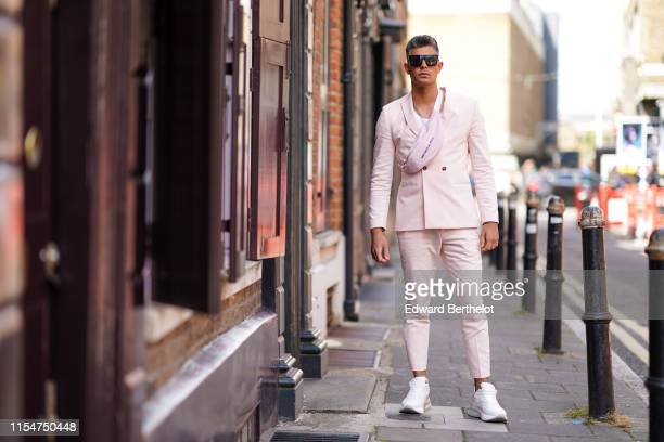 Rayer Van Ristell wears sunglasses a pink blazer jacket a fanny pack bag pink pants Alexander McQueen white and silver sneaker shoes during London...
