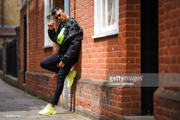 Rayer Van Ristell wears sunglasses a Valentino VLTN top a neon yellow fanny pack a black puffer jacket black pants yellow sneakers shoes during...