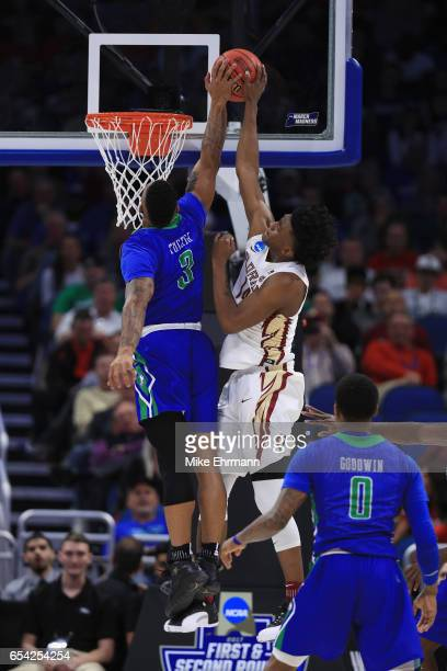 Rayjon Tucker of the Florida Gulf Coast Eagles blocks a shot by Terance Mann of the Florida State Seminoles in the first half during the first round...
