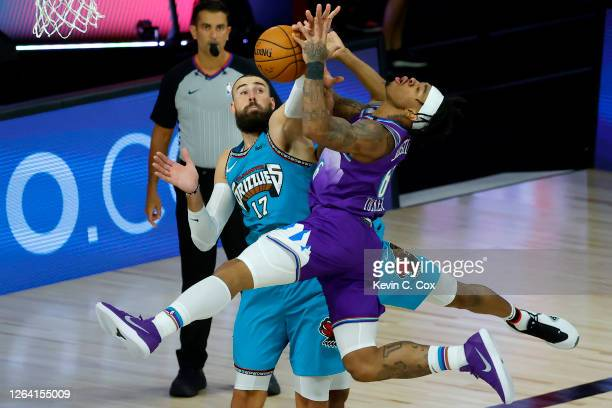 Rayjon Tucker of the Utah Jazz draws a foul from De'Anthony Melton of the Memphis Grizzlies as Jonas Valanciunas of the Memphis Grizzlies defends...