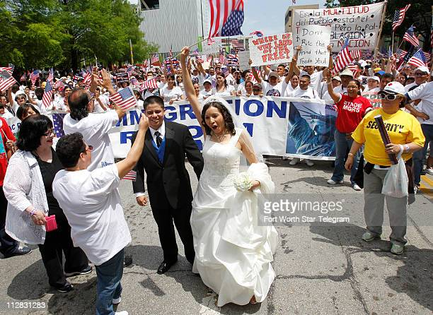 Raymond and Lucia Chavez briefly join the crowd before their wedding ceremony prior to a march from Cathedral Santuario de Guadalupe through downtown...