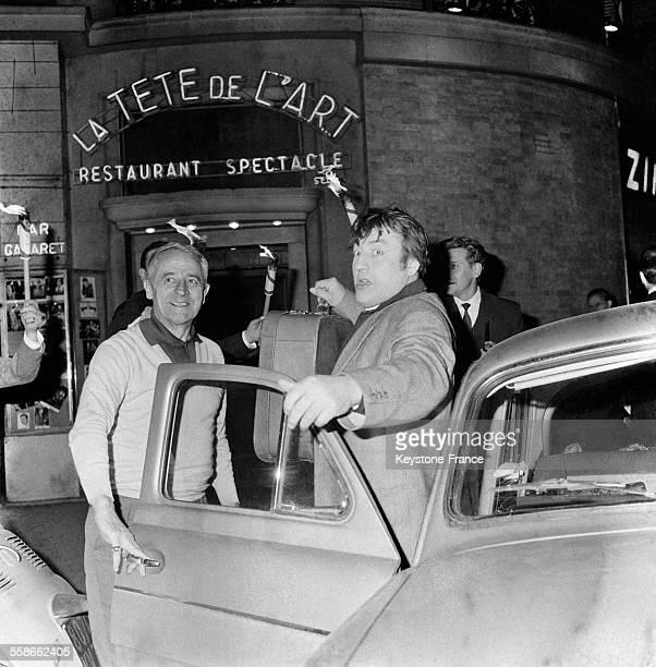 Raymond Devos accompagné du pilote automobile Jacques Blanchet arrive à la Tête de l'Art à Orly, France le 31 mai 1961.