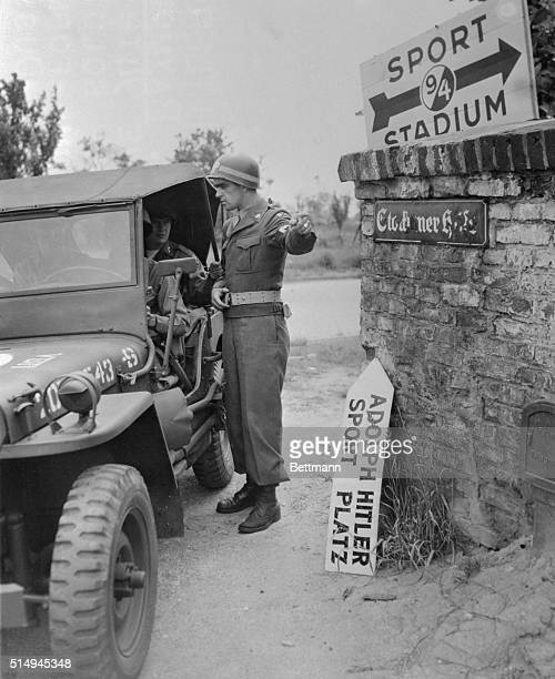 Raymond Dickinson of Alton Illinois an MP with the 94th Division in Germany directs a jeep load of soldiers to the division's sports stadiumformerly...