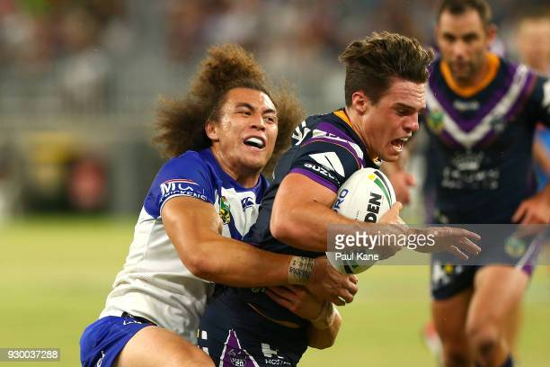 Raymond FaitalaMariner of the Bulldogs tackles Brodie Croft of the Storm during the round one NRL match between the Canterbury Bulldogs and the...