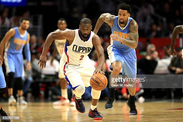 Raymond Felton of the LA Clippers dribbles past Wilson Chandler of the Denver Nuggets during the second half of a game at Staples Center on December...